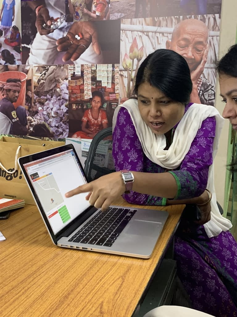 Operation ASHA staff pointing at a computer screen showing data modeled in Tableau