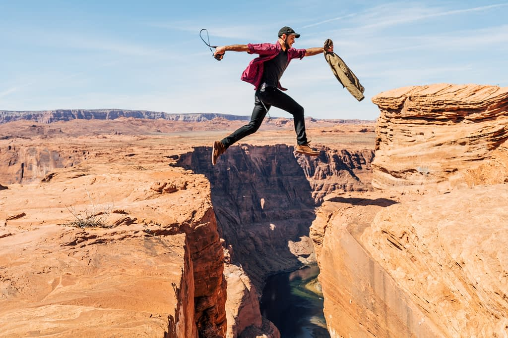 Man jumping from one side of a cliff to another