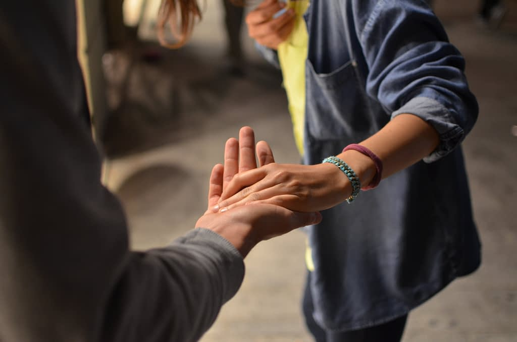 Person reaching out hand to someone else