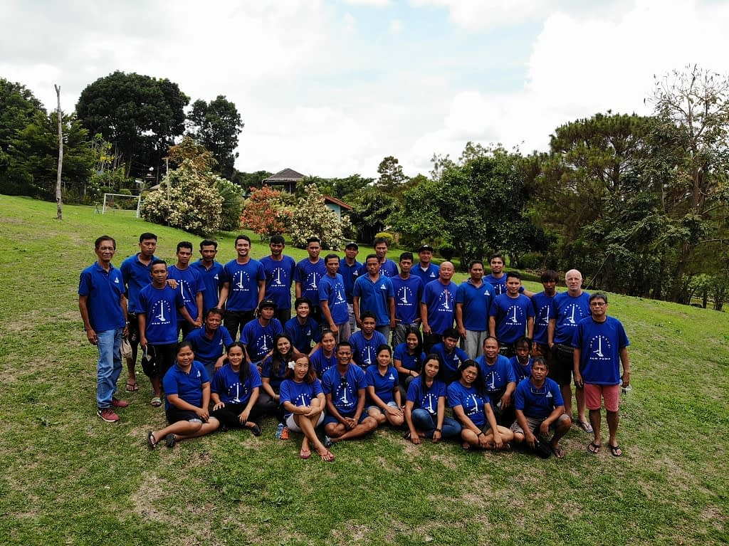 AIDFI team with volunteer, Stephen standing on a grassy hill