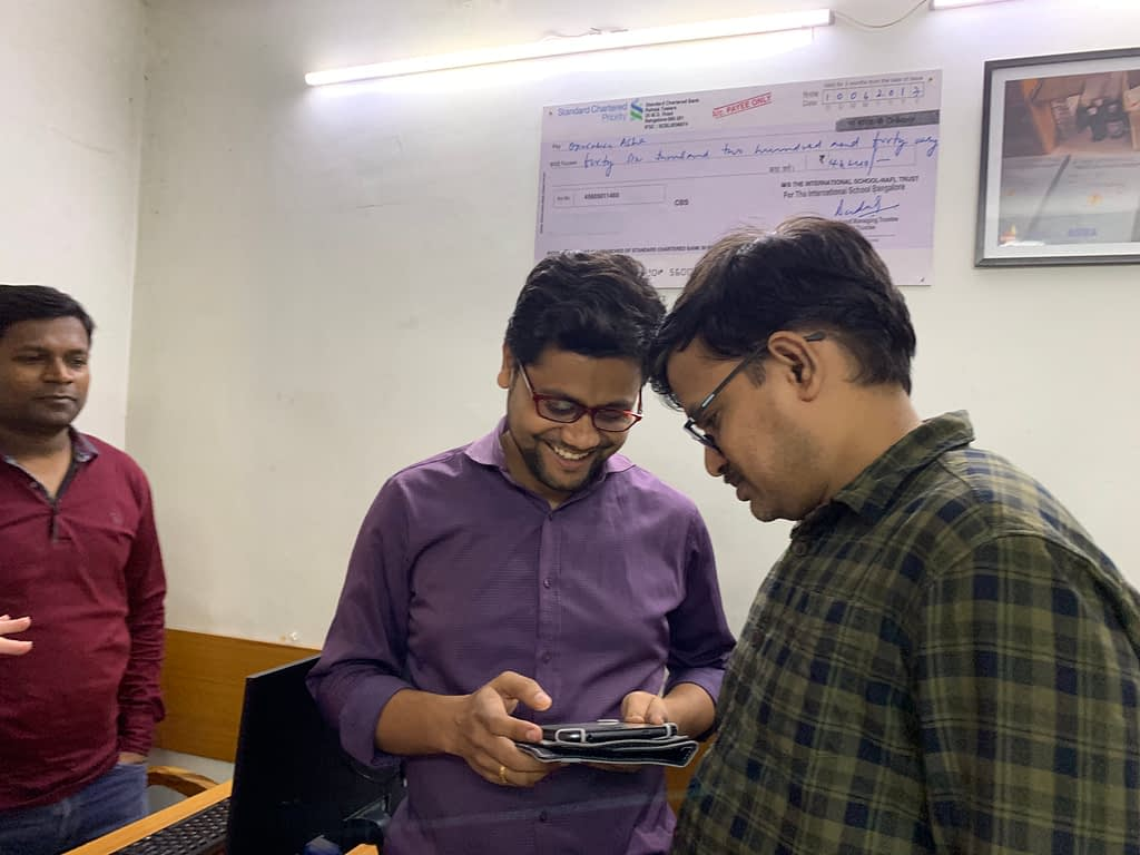 Operation ASHA staff smiling at a tablet with the Tableau app
