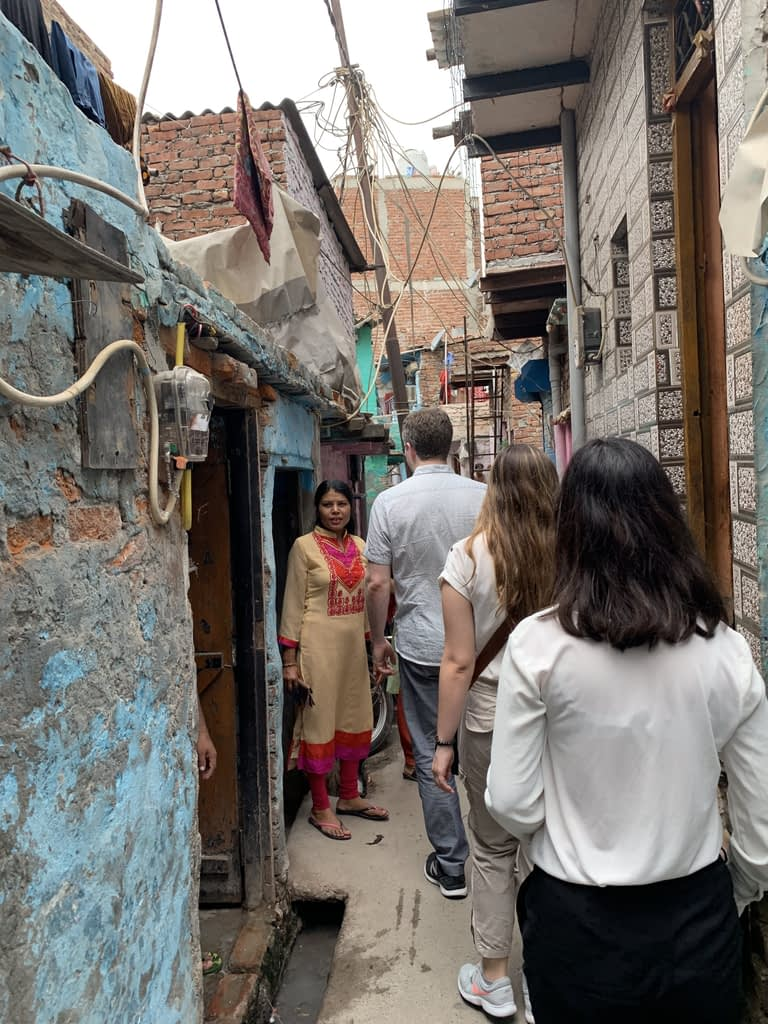 Skills-based volunteers from Tableau follow Operation ASHA staff into a crowded part of Tekhand Village in India
