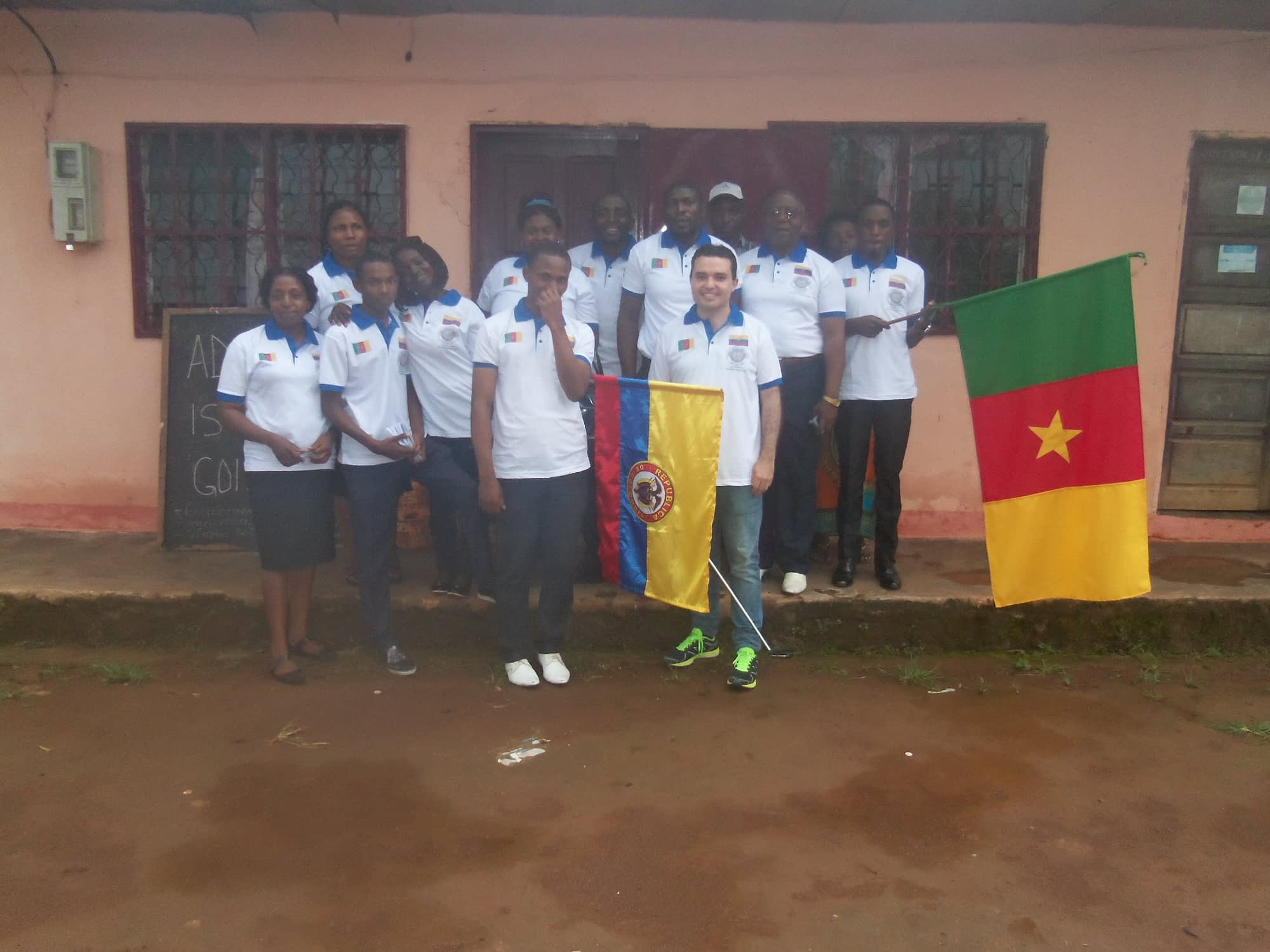 Eduardo and students outside the Tobby Vision school with the flag of Cameroon.