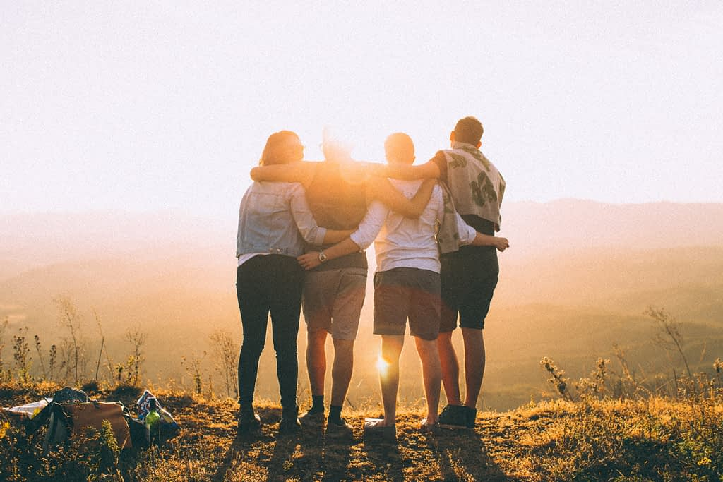Four people with arms around eachother looking ahead towards the sun