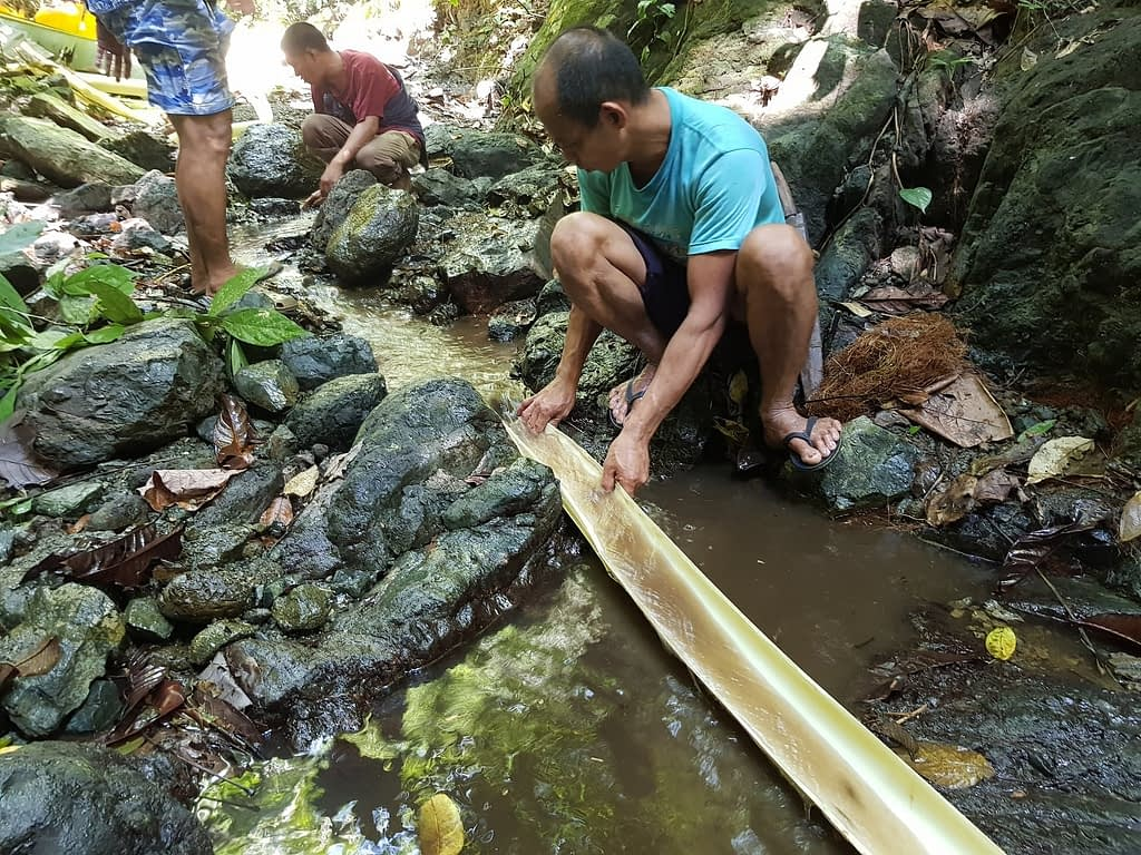 AIDFI team testing the water flow from the source for Ram Pump installation
