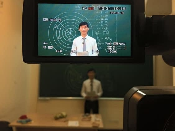 HOCMAI teacher recording a video lesson in front of a chalkboard