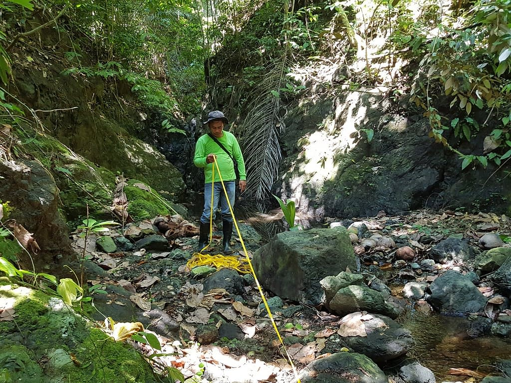AIDFI team measuring the distance from the water source to the reservoir for Ram Pump installation