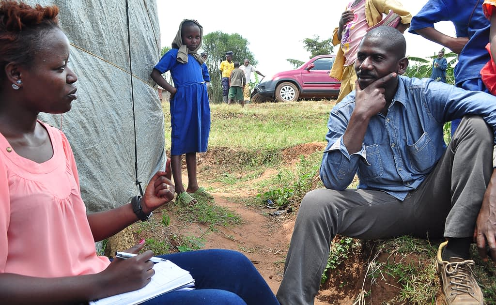 Olive Ashimwe, a business development associate at AEC, discusses potential business challenges with a coffee farmer client in Rwanda's eastern province.