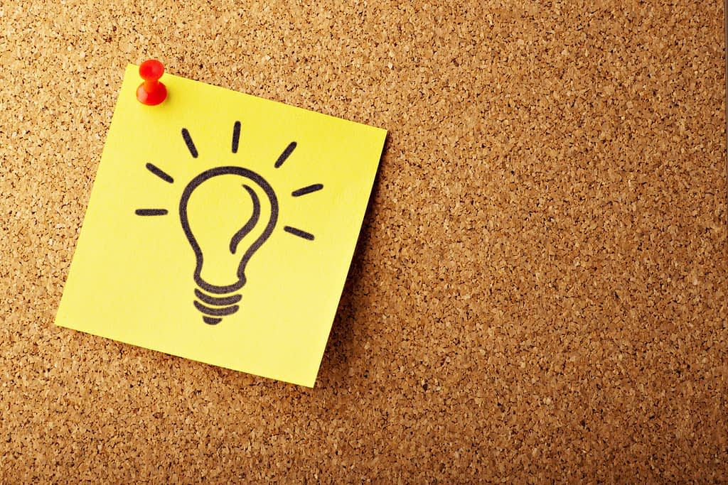 Yellow sticky note with light bulb on a cork board