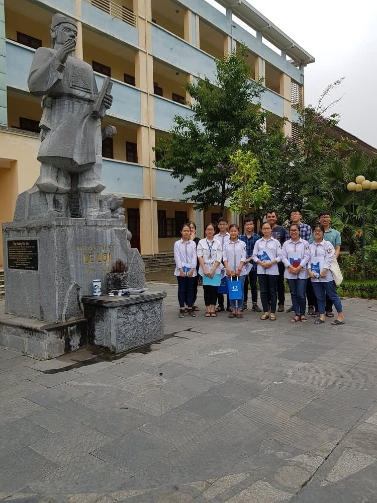 Skilled volunteer, Sam, with the HOCMAI education team standing beside a statue